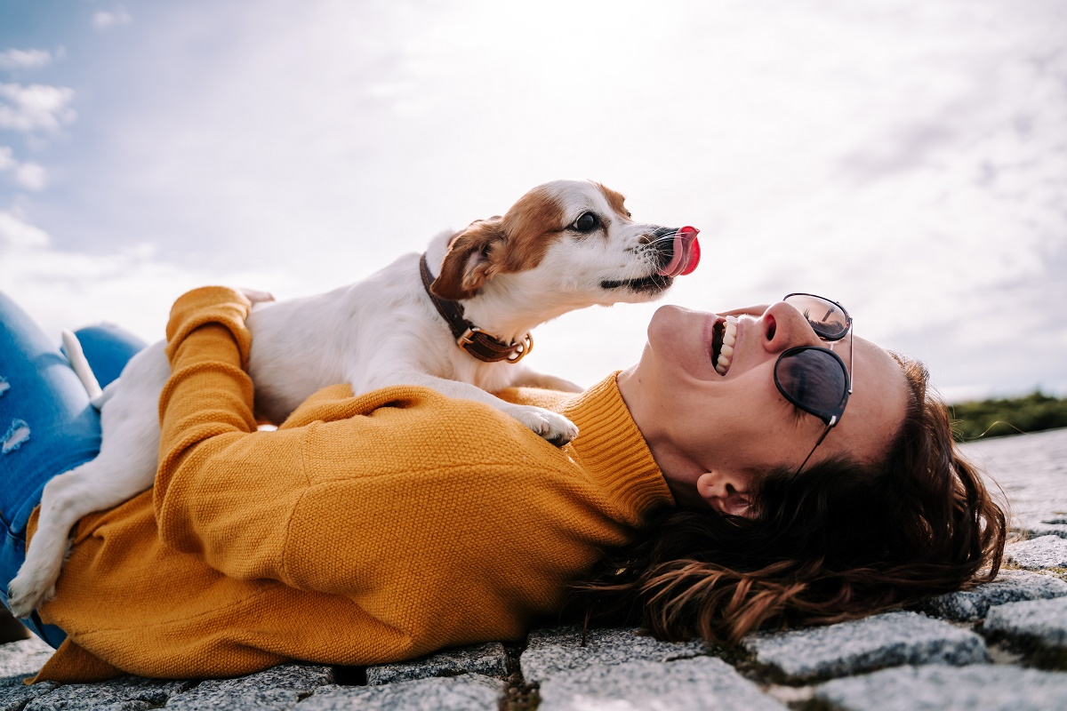 woman-laughing-while-her-pet-is-licking-her-face